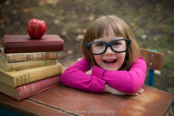young girl wears dark-rimmed glasses and sits at desk with books and apple
