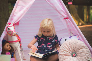 girl reading book in pink teepee tent